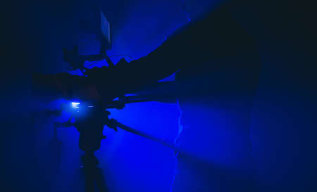 Modern Digital Camera and Filmmaking Industry Operator in Misty Room Illuminated Using Professional Film Stage Lighting. Caucasian Camera Men in His 40s. Reklamní fotografie