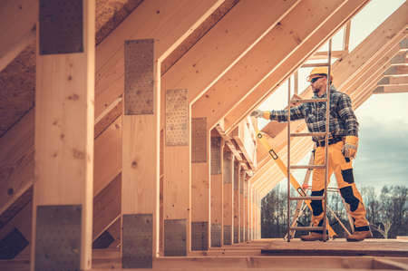 Caucasian Contractor in Hard Hat and His Residential Building Wooden Skeleton Construction Job. House Wood Frame.