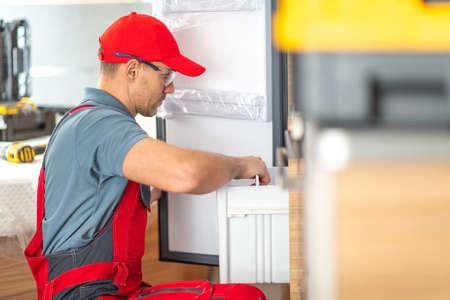 Caucasian RV Center Technician in His 40s Replacing or Repair Broken Motorhome Refrigerator. RVing Theme