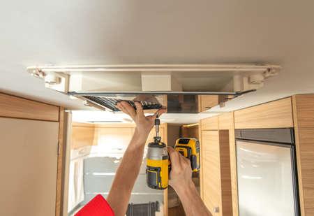 RV Recreational Vehicles Caucasian Technician Worker in His 40s Replacing Air Conditioner Unit Inside Modern Motorhome. Reklamní fotografie