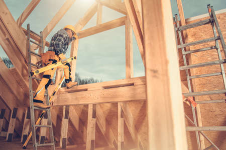 Second Level of Wooden Skeleton Frame of House Construction. Professional Industry Worker with Spirit Level Tool in His Hand. Industrial Theme. Reklamní fotografie