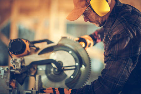 Professional Construction Contractor Worker Using Powerful Circular Wood Saw in Construction Zone. Wearing Safety Glasses and Noise Reduction Headphones. Industrial Theme.