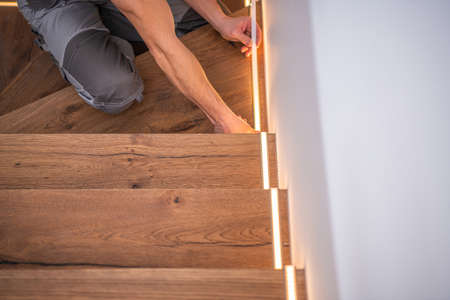 Professional Caucasian Worker Finishing LED Residential Wooden Stairs Lights Installation. Modern Home Illumination Technologies.