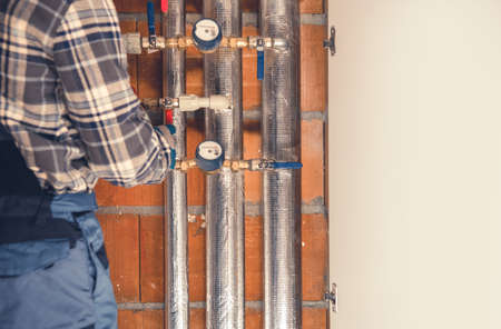Heating System Final Adjustment Performed by Technician. Pipelines, Valves and Counters of Residential Heating System. Industrial Theme. Фото со стока