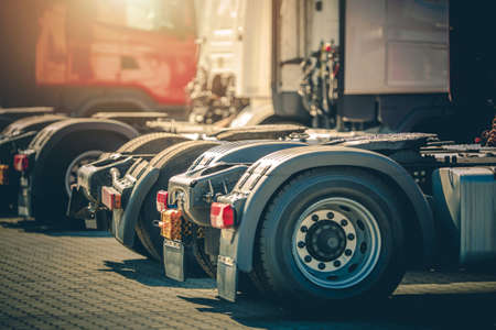 Modern Brand New Semi Truck Tractors in Line on Dealership Parking Lot. Heavy Duty Transportation and Automotive Industry Theme. Фото со стока