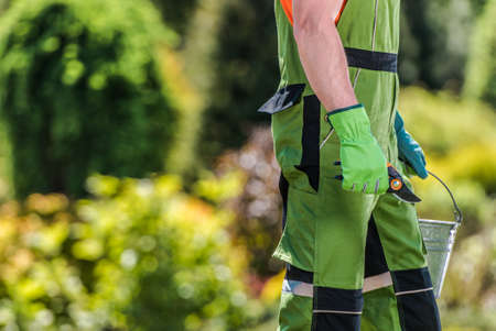 Caucasian Gardener in His 40s with Branch Trimming Tool in His Hand Lower Body Part Close Up. Gardening and Landscaping Theme.