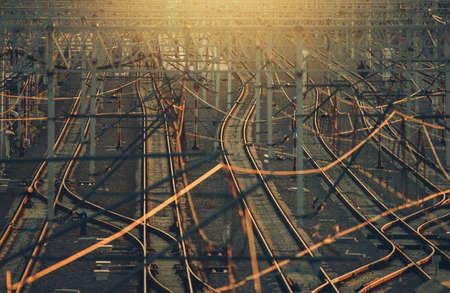 Modern Railroad Infrastructure with Multiple Rail Tracks During Sunset. Telephoto Perspective.