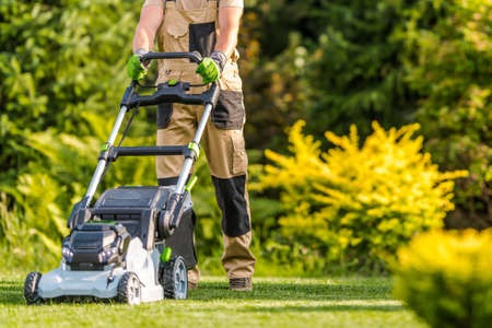 Caucasian Garden Worker in His 40s Cutting Grass Using Modern Electric Cordless Lawnmower in Large Backyard Garden. Landscaping Industry Theme.