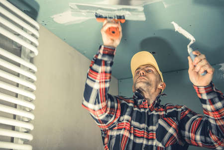 Caucasian Construction and Remodeling Worker in His 40s Patching Bathroom Ceiling and Preparing Walls For Painting.