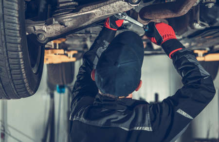 Transportation and Automotive Theme. Modern SUV Car Suspension Maintenance Performed by Caucasian Car Mechanic.