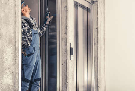 Caucasian Residential Elevator Technician in His 40s Performing Scheduled Maintenance. Фото со стока