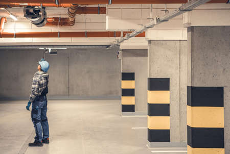 Caucasian Air Ventilation Technician in His 40s Checking on New Underground Garage Polluted Air Removal Installed on a Garage Ceiling. Industrial Theme.