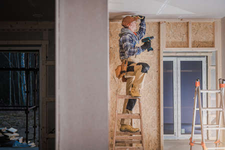 Caucasian Construction Worker In His 40s Installing Drywall Ceiling Elements in the Newly Developing Residential Wooden Skeleton Frame Made Building. Construction Industry Theme. Фото со стока