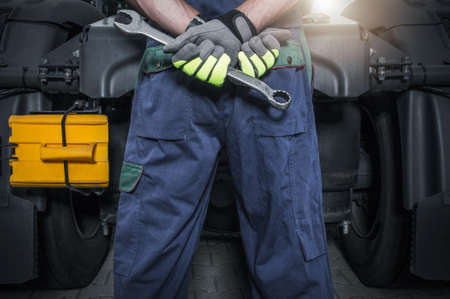 Truck Mechanic in Front of Tractor with Wrench in His Hands Staying Back to Camera. Lower Body Close Up. Trucking Industry Theme.