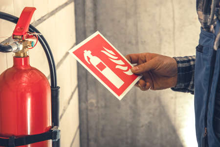 Fire Extinguisher and Required by Law Wall Sings Installation Inside Commercial Building by Caucasian Worker