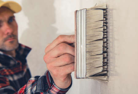 Caucasian Worker in His 40s Walls Priming Using Large Painting Brush Close Up. Refreshing Apartment Interiors. Home Remodeling Theme. Фото со стока