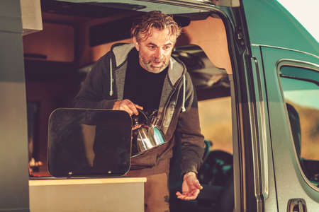 Caucasian Men in His 50s with Water Kettle Inside Camper Van Preparing Hot Water For Late Afternoon Tea Time. Recreational Vehicle Traveling.