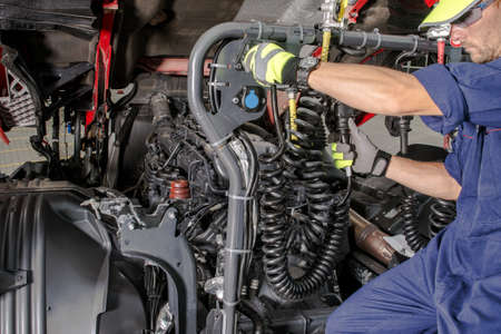 Caucasian Semi Truck Mechanic Performing Diesel Engine Maintenance with Scheduled Checkup. Transportation Industry Theme. Фото со стока