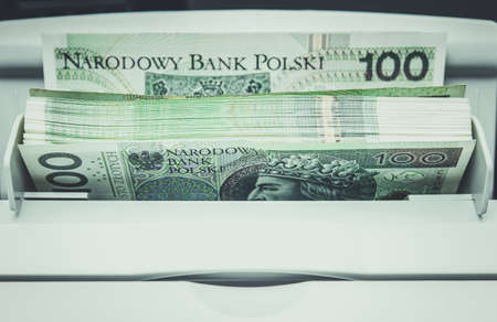 One Hundred Polish Zloty Currency Banknotes Inside Bills Counting Machine.