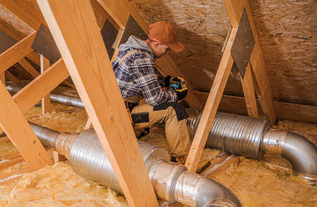 Caucasian HVAC Heating and Cooling Technician in His 40s Installing System Elements in the Home Attic.