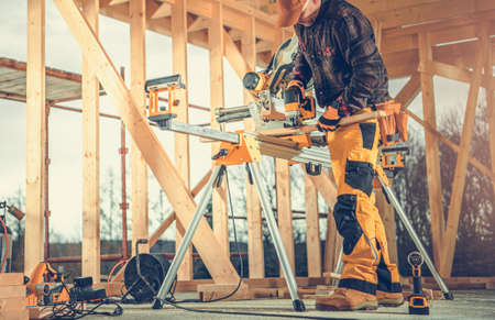 Caucasian Contractor in His 40s Cutting Small Wood Elements. Wooden Skeleton Frame of House Construction.