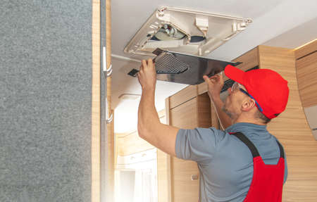 Caucasian RV Appliances Technician in His 40s Repairing Air Condition Unit Inside Modern Travel Trailer. Recreational Vehicles Industry Theme.