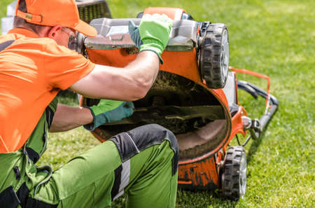 Professional Caucasian Landscaper in His 40s Checking on Lawn Mower Blade While Cutting Client's Backyard Garden Grass Field. Фото со стока