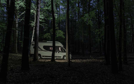 RV Recreational Vehicle Theme. Modern Camper Van Camping Inside the Forest During Night Time.