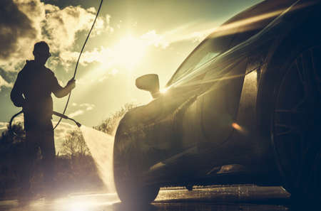 Caucasian Driver in His 40s Power Pressure Washing His Performance Car During Sunset Golden Hour. Vehicle Maintenance.