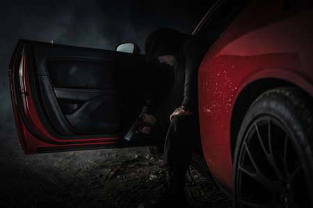 Pensive Caucasian Gangster in His 40s Wearing Black Hoodie with Handgun in His Hand Inside Red Muscle Car. Illegal Activity Theme.