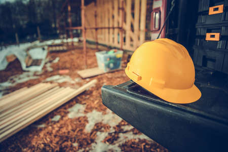 Hard Hat Construction Zone. Yellow Plastic Hard Hat Laying on Edge of Pickup Truck Platform. Wooden Skeleton Frame of Building in a Background. Construction Industry Theme.