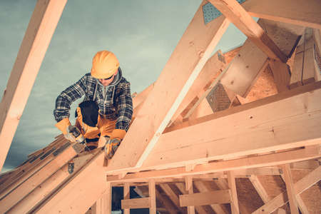 Wooden House Roof Beams Assembly by Construction Worker in His 40s. Construction Industry Theme.
