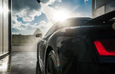 Powerful Pressure Washing Performance Car After Racing Day. Car Wash Theme. Automotive Industry. Фото со стока