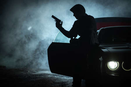 Caucasian Pensive Gangster in His 40s Playing with His Handgun During Late Night. Seating on His Car Hood. Drama and Darkness. Outlaw Theme.