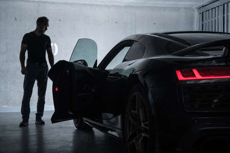 Successful Caucasian Men in His 40s Looking at His Luxury Exotic Car Inside Underground Garage. Car Enthusiast Collection. Фото со стока