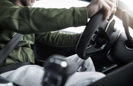 Caucasian Men Behind the Car Steering Wheel. Driving Performance Vehicle. Interior View. Фото со стока