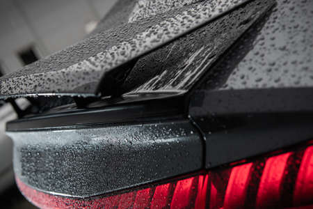 Automotive Theme. Detailed Modern Car Washing. Luxury Vehicle Spoiler and Tail Lights Covered by Water Drops Right After Washing Close Up Фото со стока