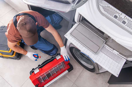 Residential Washing Machine Fixing by Caucasian Professional Technician. Home Appliances Issues Theme.