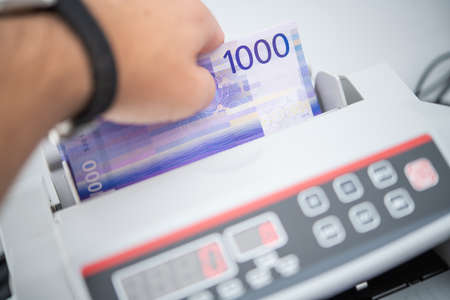 Caucasian Bank Worker and Norwegian Krone Bills Counting Using Money Counter. Financial Theme. Reklamní fotografie