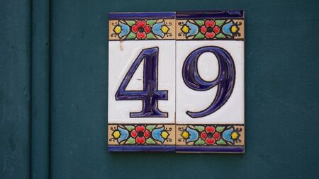 House number forty-ine 49 painted on ceramic tile in blue and yellow, red and gold from Israel
