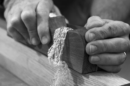 carpenter's sawdust: Close-up of woodworkers hands using a plane to smoothe a board Stock Photo