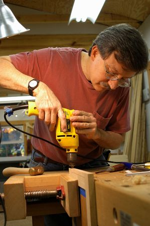 Woodworker using an electric drill to make a hole Banco de Imagens