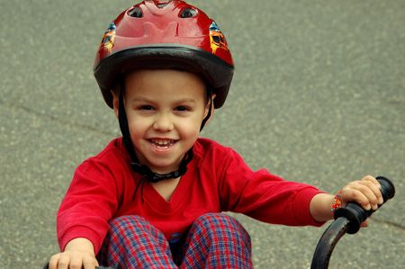 Close in shot of a young child wearing a helmet sitting on his bicycle