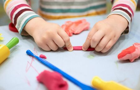 Child hands playing with colorful clay.