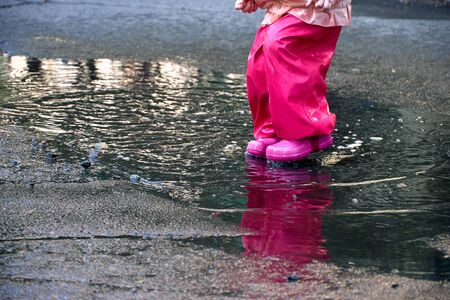 Happy child jumping in puddle in waterproof coat. A girl have fun in the rain weather in a bright raincoat. Legs of child with rubber boots.