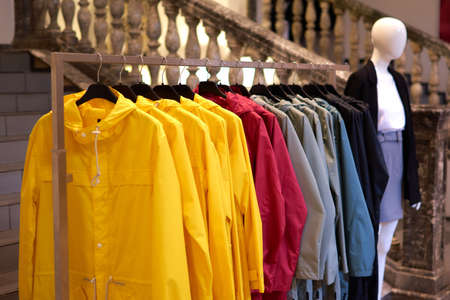 Bright colorful autumn raincoats hanging at a fashion store. Closeup of multi-colored yellow, red, grey, waterproof raincoats hang in a row on a hanger at clothes shop in the shopping mall. Imagens