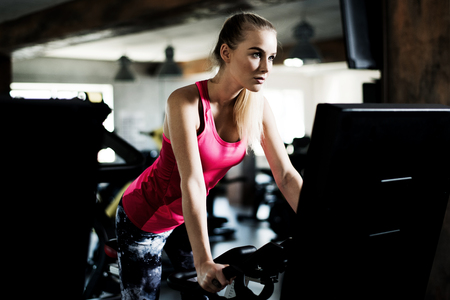 Attractive young woman is exercising in a gym