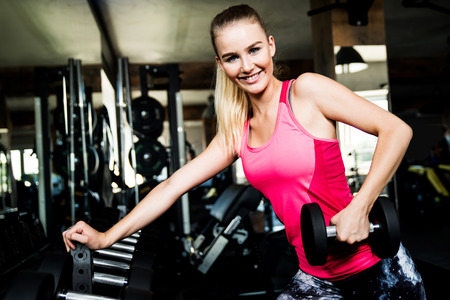 Attractive sporty woman is exercising with dumbbells