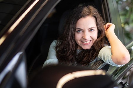 Young woman laughing happily in a car