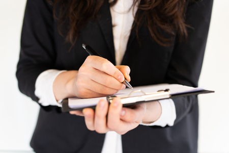 Business woman is writing something on a clipboard